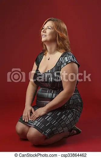 Kneeling woman. Woman wearing a cocktail dres kneeling down.