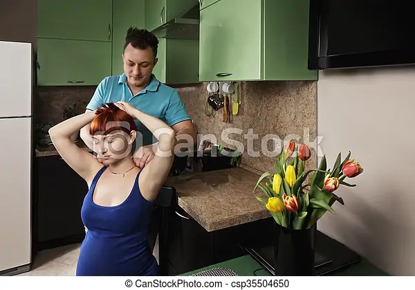 Man making neck massage to pregnant woman at the kitchen.