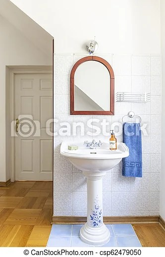 Old fashioned free standing china wash basin with a mirror above in a classic bathroom interior. real photo.