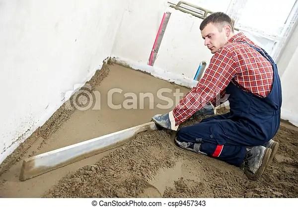 Plasterer concrete worker at floor work. Plasterer at indoor concrete cement floor topping with screed sleeker.