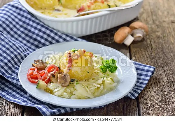 Potato dumpling gratin on coleslaw. Hearty potato dumpling gratin with cheese and bacon served on warm coleslaw.