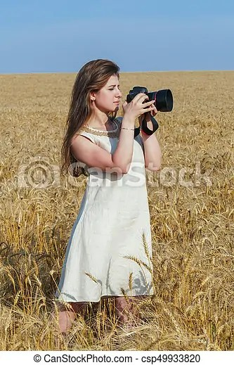 Pretty Girl Taking Photos With Big Black Camera On The Field