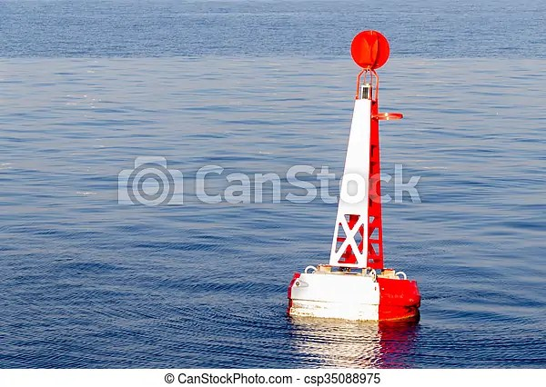 Red white moored buoy in blue ocean.