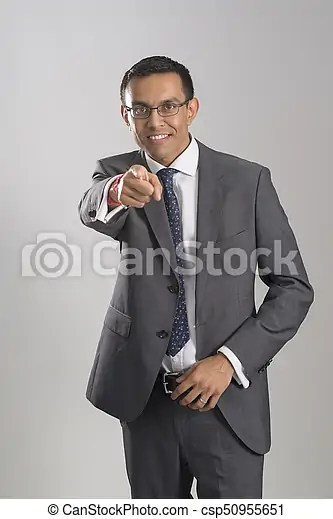 Smiling Guy In Business Suit Staring And Pointing A Finger Smiling Guy In A Business Suit Staring And Pointing A Finger