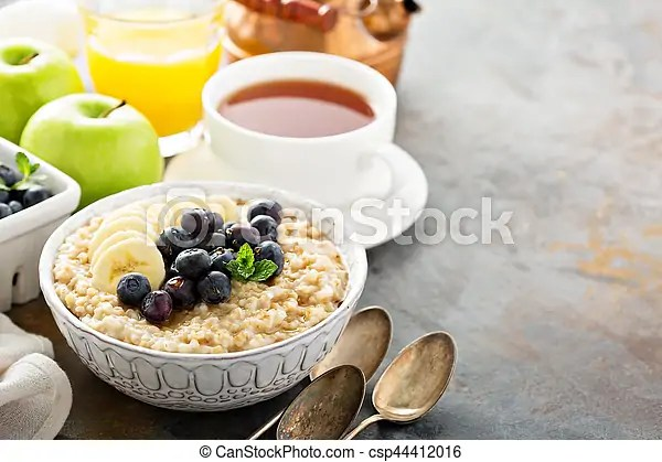 Steel cut oatmeal porridge with banana and blueberry for breakfast with copyspace.