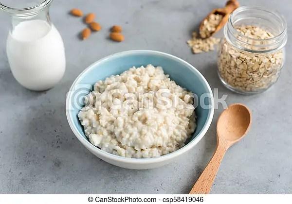 Steel cut oats, oatmeal porridge in bowl. healthy breakfast on grey concrete table background.