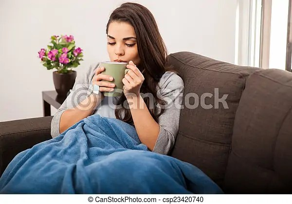 Taking a sip of tea. Cute young brunette covered in a blanket on a cold day enjoying a cup of tea.
