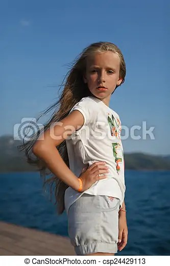 The portrait of the young girl about 9-12 years old with the blonde and loose hair that stands on the pier in the rays of the setting sun with ...