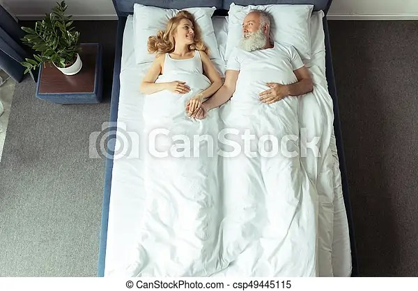 https www canstockphoto com top view of smiling couple lying in bed 49445115 html