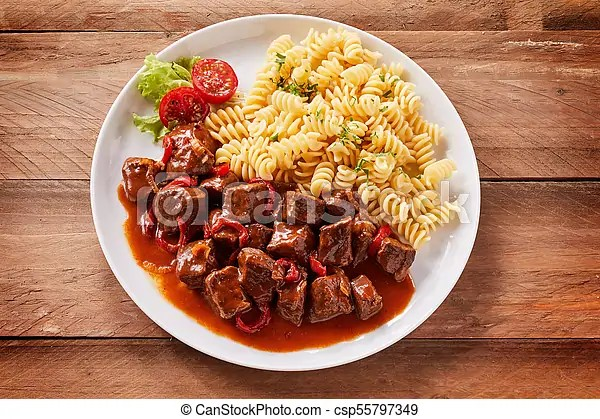 Traditional german beef casserole with spicy sauce served alongside corkscrew pasta.