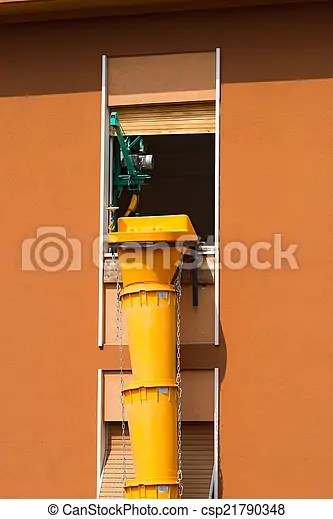 Waste debris chute - construction site. Flexible pipe in yellow plastic for removing construction waste in construction site.