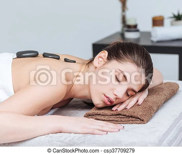 Woman Relaxing And Receiving Hot Stone Massage In Spa Salon Csp