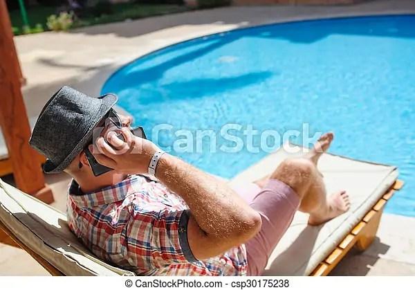 Telfono hablar piscina lounger sombrero acostado hombre Hablar telfono piscina