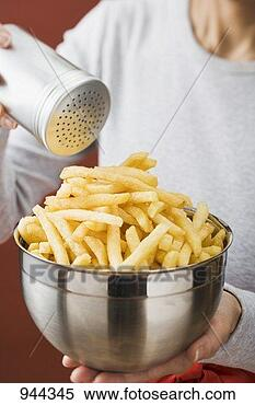 Stock Image - putting salt on  chips in a bowl.  fotosearch - search  stock photos,  pictures, images,  and photo clipart