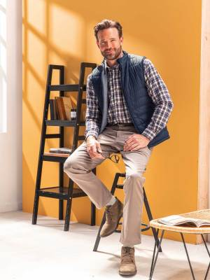 La tenue tendance : chemise flanelle, doudoune sans manches et pantalon taupe élastiqué