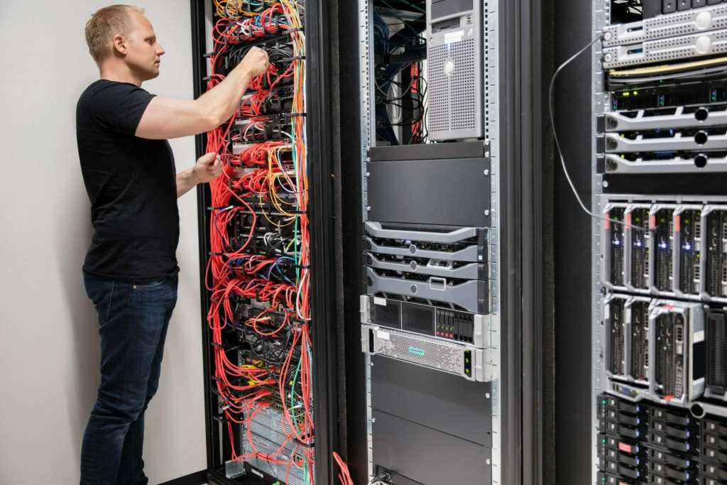 IT technician checking wiring of a server