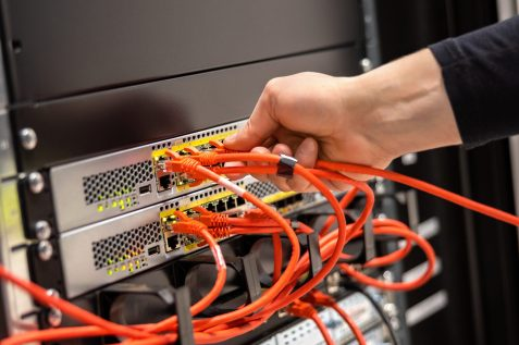 Cropped hand of male technician plugging network cable in router cluster at datacenter