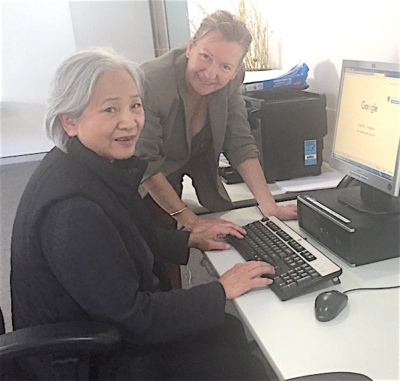 Zoe from Computer Coach Australia working on a computer with a senior
