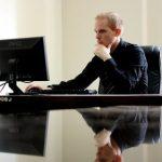 man-sitting-at-desk-looking-at-computer-monitor