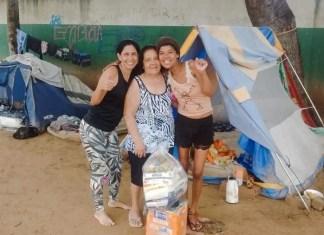 Arinda e a nora entregam cestas básicas à mulher em situação de rua