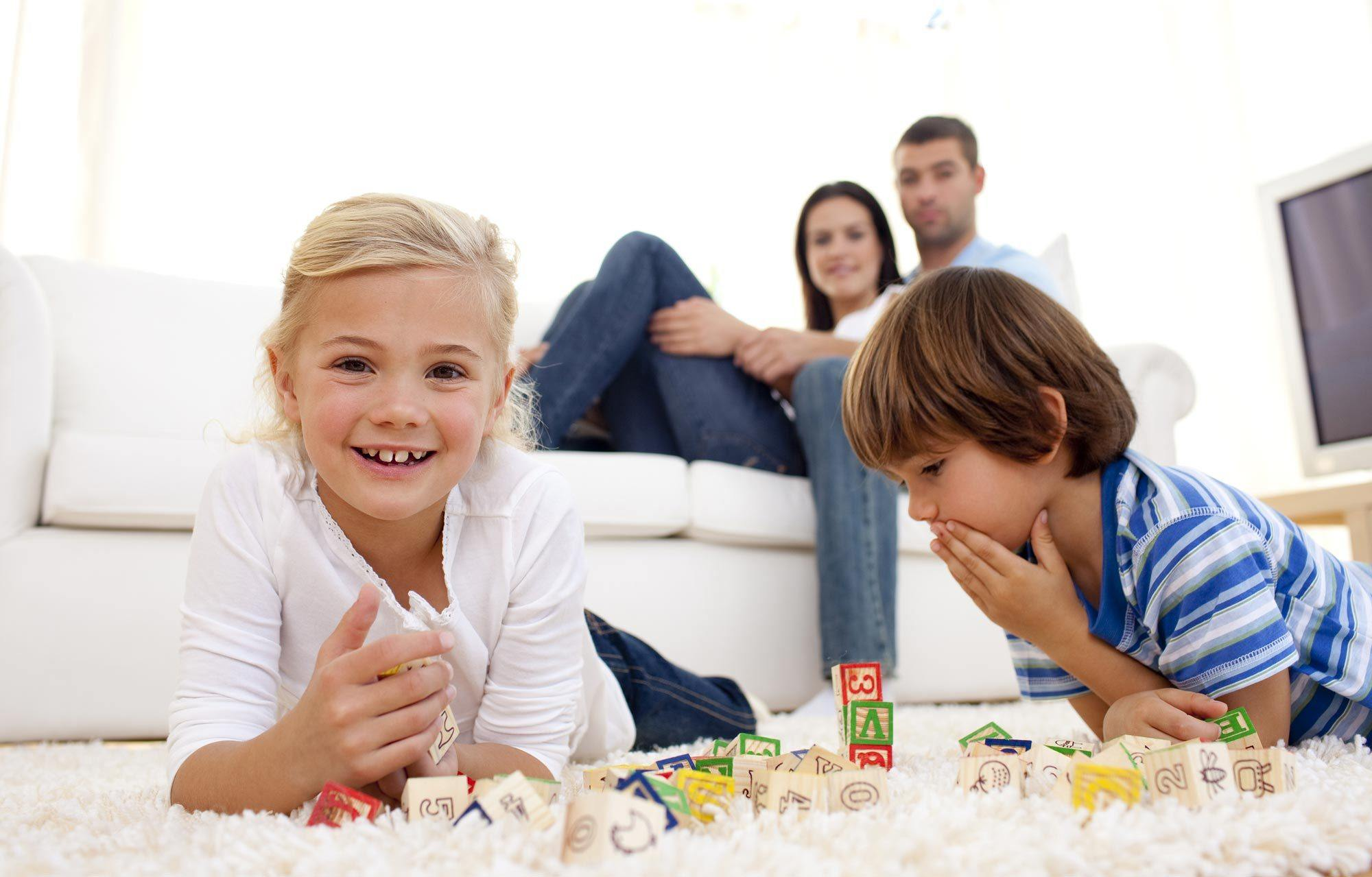 Children playing with blocks on the floor while their parents watch from the couch
