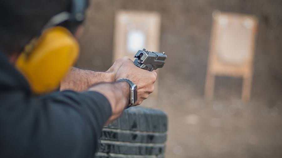 A man holding a firearm pointed at a target