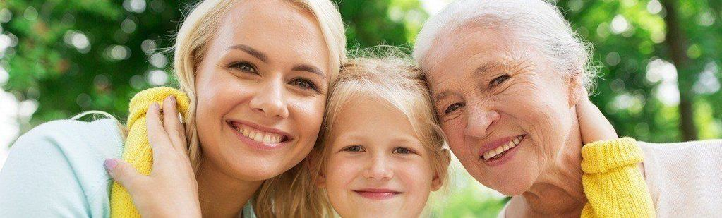 A child with her mother and grandmother smiling