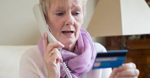 An elderly woman on the phone who has fallen victim to credit card scams
