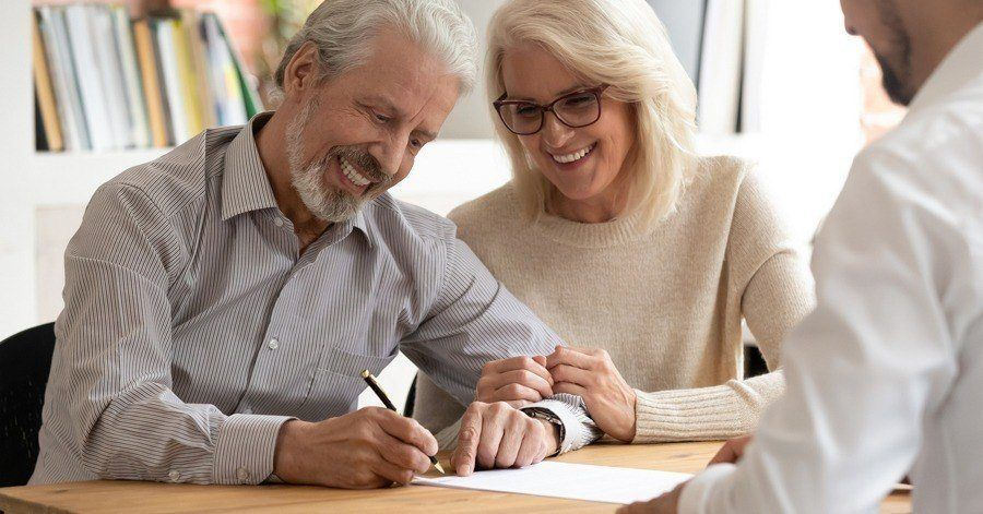 A couple signing their long term care insurance policy