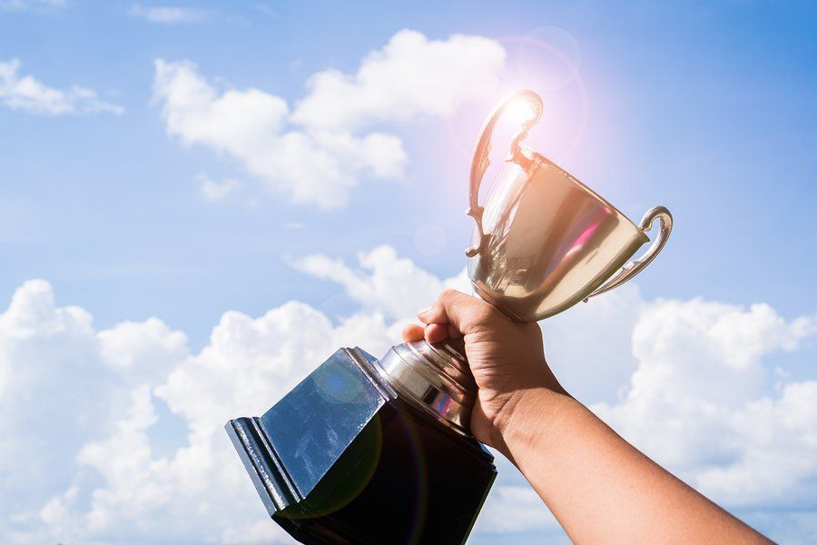 A person holding a trophy to the sky