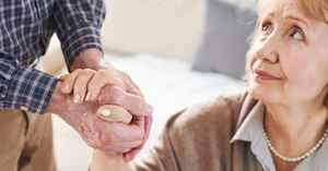 A caregiver managing their stress and maintaining a quality relationship with their loved one by holding her hand