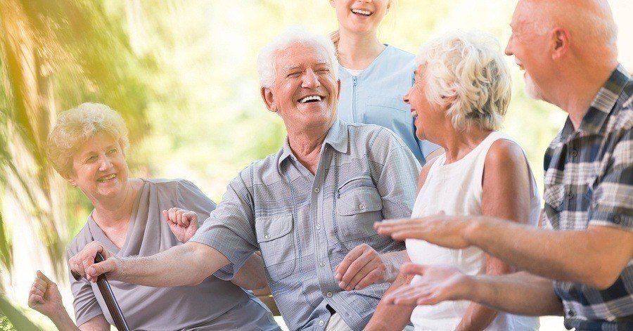 A group of elderly people laughing in a nursing home