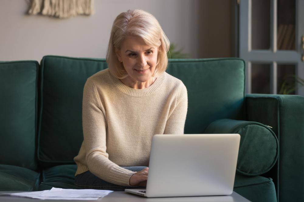 An elderly woman enrolling for medicare on her laptop