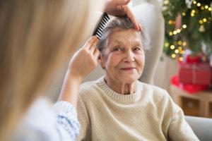 A Health Visitor Combing Hair Of Senior Woman At Home At Christmas