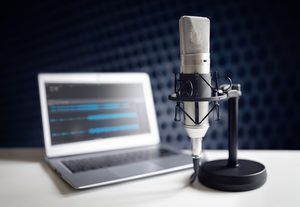 Podcast microphone and laptop computer on desk in recording studio