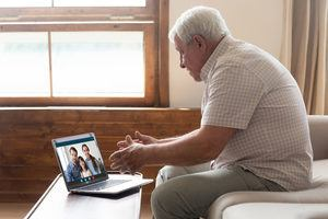 Happy elderly man holding video call with family.