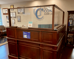 A desk at Cona Elder Law with plexiglass to abide by Covid-19 safety protocols