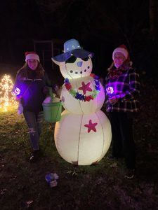Two people with a beach themed blow up snowman