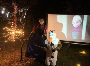 People dressed up as Princess Anna and Olaf posing in front of a movie screen
