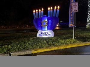 A blow up Menorah that says happy Hanukkah