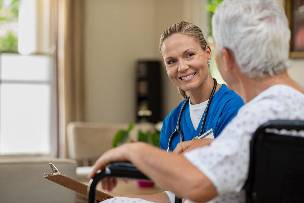 Happy smiling nurse consulting disabled patient about treatment.