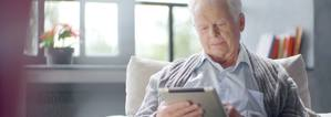 An elderly man joining a virtual meeting from his iPad