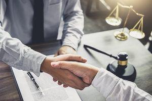 Businessmen shaking hands after winning a Medicaid settlement