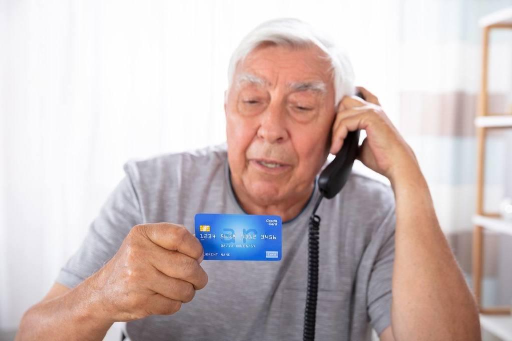 A senior citizen on the phone holding a credit card avoiding financial fraud