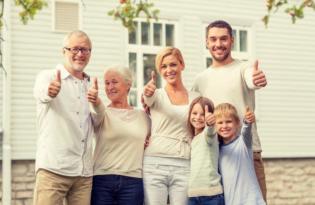 Happy family smiling with their thumbs up