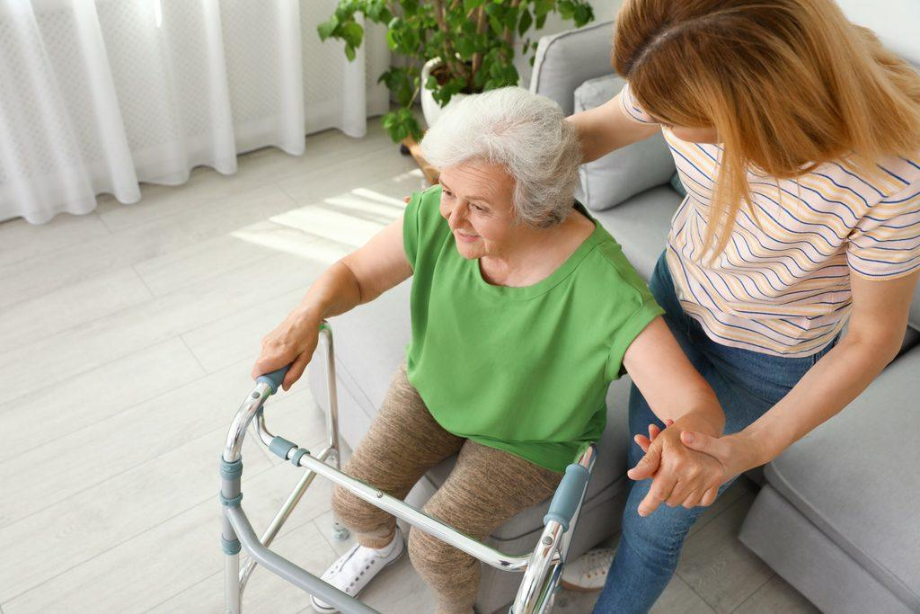 An elderly woman being assisted by her caretaker in a nursing home