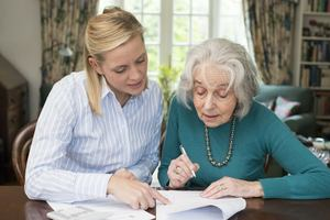 A senior citizen reviewing legal documents with her elder law attorney