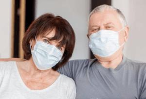 Older couple sitting together wearing masks