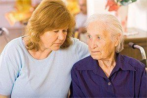 A concerned looking lady with an elderly person in a wheelchair inside a nursing home.