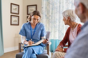 Nurse talking to old patients while being in a nursing home